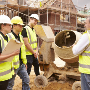 Builder Using Cement Mixer On Building Site With Apprentices